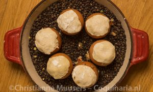 The eggs on a layer of lentils in the oven dish before baking