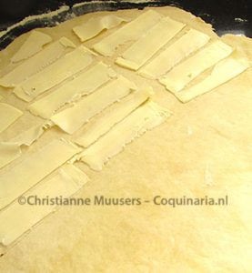 De boter wordt in dunne plakjes op het uitgerolde deeg gelegd
