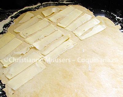 Op het uitgerolde basisdeeg worden plakjes koude boter gelegd