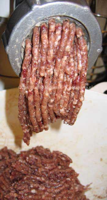 Het vlees voor de farce wordt gemalen. De witte stukjes zijn vet spek en witbrood, de donkerrode varkenslever.