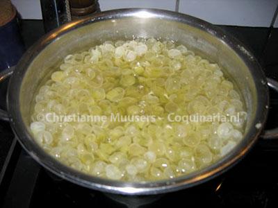 De vliesjes om de groene erwten komen tijdens het koken bovendrijven