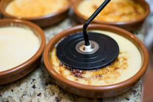 Burning crema catalana with an old-fashioned burning iron. Picture Paul Goyette (Flickr)
