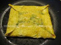 De omelet met het extra ei erop, vlak voor het keren