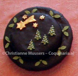 Kerstcake met zwart glazuur en vergulde sterren