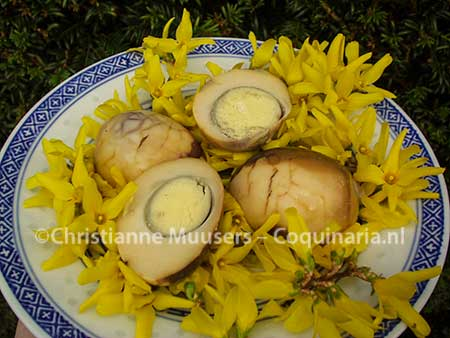 Chinese tea eggs on a layer of flowering Forsythia